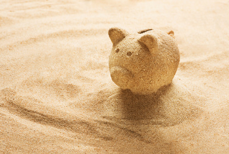 calmness: Piggy bank sculpted in sand on sandy beach Stock Photo