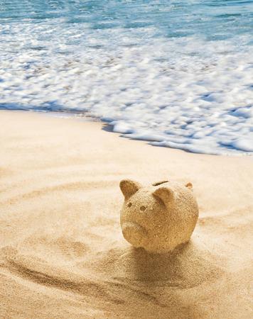bank activities: Piggy bank sculpted in sand on sandy beach Stock Photo