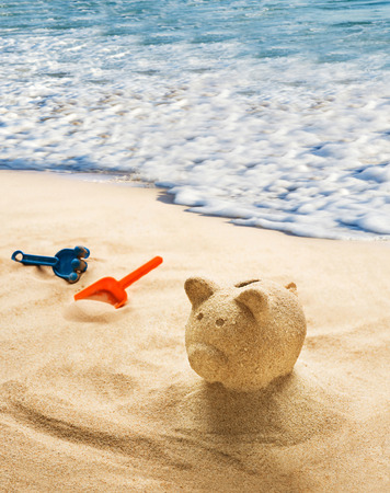 bank money: Piggy bank sculpted in sand on sandy beach Stock Photo