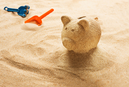 Piggy bank sculpted in sand on sandy beach Banque d'images