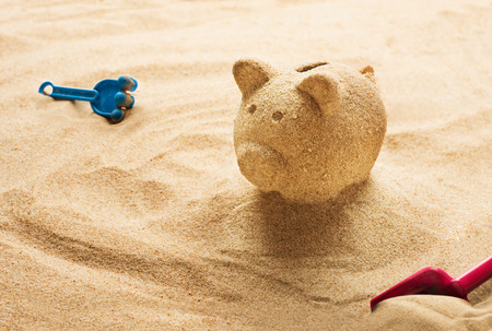 Piggy bank sculpted in sand on sandy beach Standard-Bild