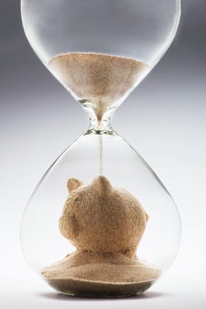 planificación familiar: Concepto de los ahorros con la caída de la arena tomando la forma de una alcancía