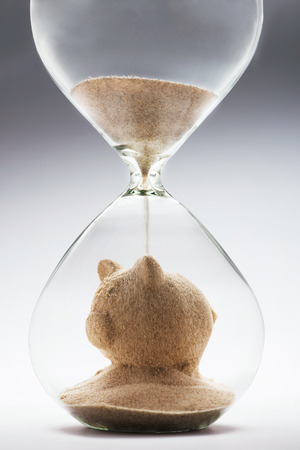 Savings concept with falling sand taking the shape of a piggy bank Stok Fotoğraf