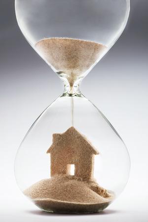 reloj de arena: Verano concepto de alojamiento con la caída de la arena tomando la forma de una casa