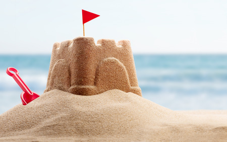 holiday destination: Holiday concept with sandcastle on the seaside