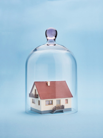 subprime mortgage crisis: Home safety. A model home protected under a glass dome on blue background