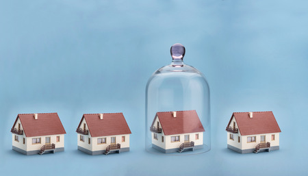 dome: Home safety. A model home protected under a glass dome on blue background