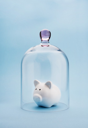 bank protection: Piggybank protected under a glass dome on blue background Stock Photo