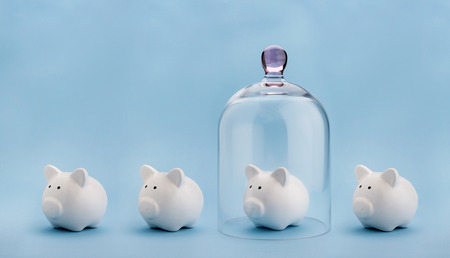 Piggybank protected under a glass dome on blue background Stockfoto