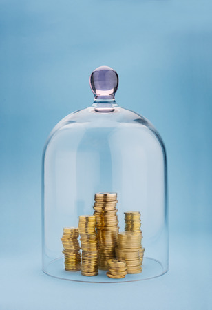 Coins stacks protected under a glass dome on blue background Banco de Imagens