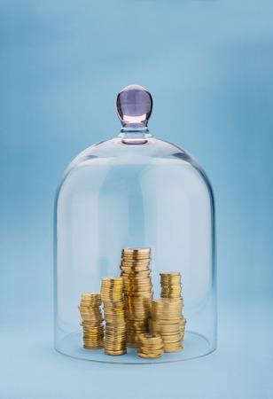 elementos de protecci�n personal: Monedas pilas protegidos bajo una c�pula de vidrio sobre fondo azul
