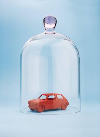caja fuerte: Coche de juguete protegido por una cúpula de cristal sobre fondo azul Foto de archivo