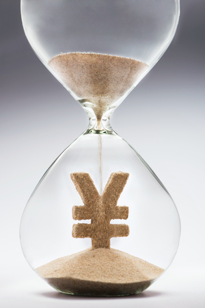 Time is money concept with hourglass falling sand taking the shape of a yenyuan Stock Photo