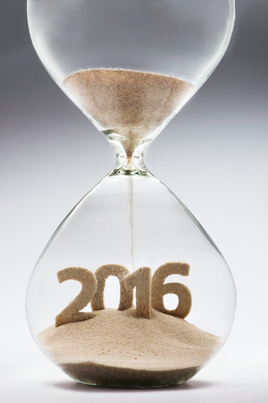 turns of the year: New Year 2016 concept with hourglass falling sand taking the shape of a 2016 Stock Photo