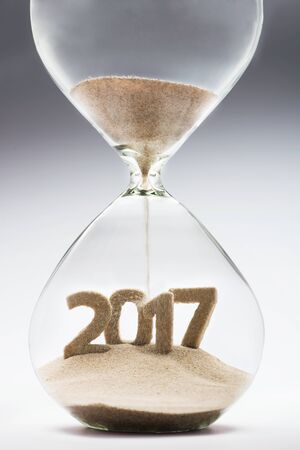 turns of the year: New Year 2017 concept with hourglass falling sand taking the shape of a 2017