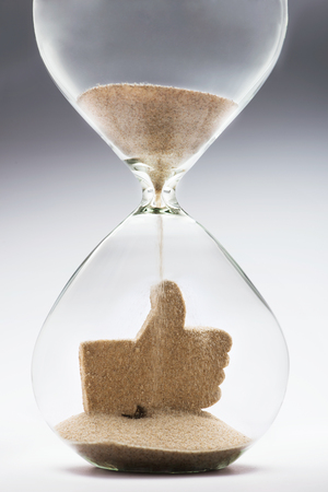 interactivity: Like icon made out of falling sand inside hourglass Stock Photo
