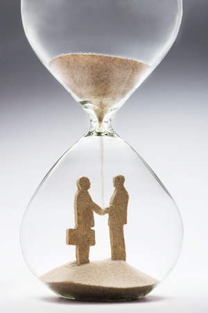 Two businessmen shaking hands made out of falling sand inside hourglass