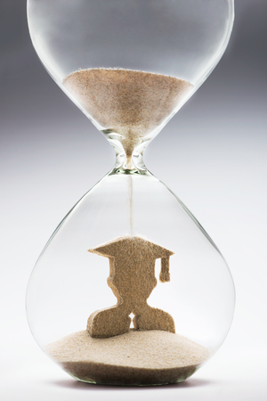 graduation countdown: Graduate figure made out of falling sand inside hourglass