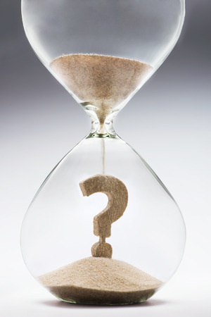 question marks: Future uncertainty. Question mark made out of falling sand inside hourglass