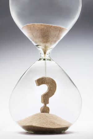 reloj de arena: Incertidumbre futura. Signo de interrogación hecho de la arena que cae dentro del reloj de arena