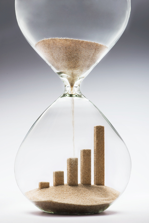 market trends: Business growth graphic bar made out of falling sand inside hourglass Stock Photo