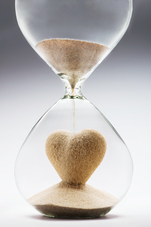 Heart shape made out of falling sand inside hourglass