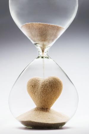 Heart shape made out of falling sand inside hourglass