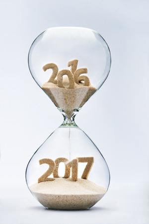 turns of the year: New Year 2016 concept with hourglass falling sand taking the shape of a 2017