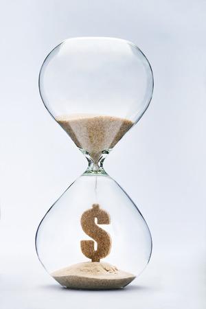 reloj de arena: El tiempo es el concepto de dinero con la caída de la arena tomando la forma de un dólar