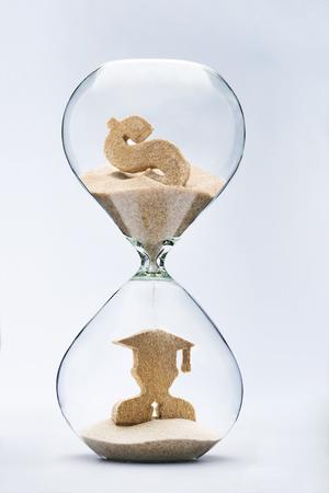 convivencia escolar: Figura graduado hace fuera de la arena que cae de la muestra de dólar que fluye a través del reloj de arena Foto de archivo