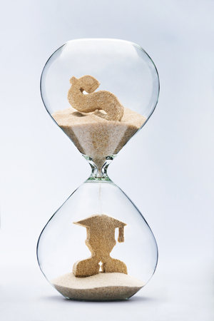 Graduate figure made out of falling sand from dollar sign flowing through hourglass