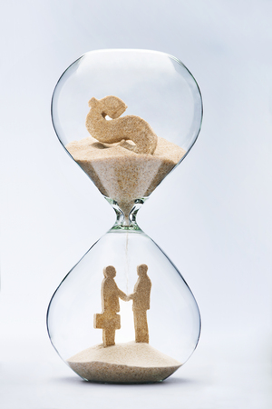 investment solutions: Business deal. Two businessmen shaking hands made out of falling sand from dollar sign flowing through hourglass Stock Photo