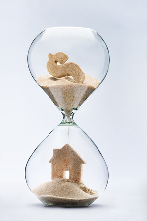 housing crisis: Hourglass house mortgage concept.House made out of falling sand from dollar sign flowing through hourglass