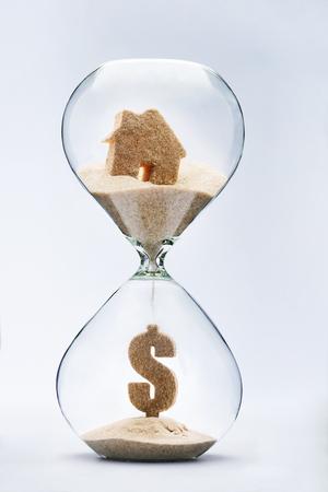 reloj de arena: Concepto de bienes raíces. Muestra de dólar hecha de arena que cae desde la casa que fluye a través del reloj de arena