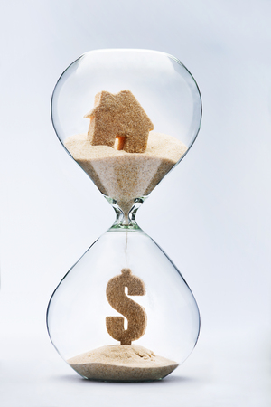 foreclosed: Real estate concept. Dollar sign made out of falling sand from house flowing through hourglass