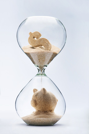 Banking concept. Piggy bank made out of falling sand from dollar sign flowing through hourglass