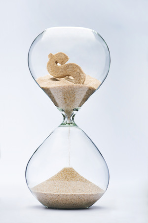 sands of time: Time is money. Dollar sign flowing down in the hourglass.