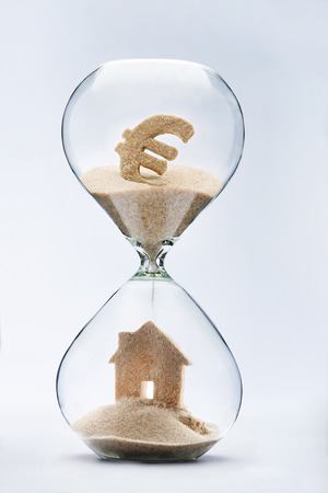 Hourglass house mortgage concept. House made out of falling sand from euro sign flowing through hourglass 스톡 콘텐츠