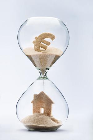 Sanduhr Haus Hypothek Konzept. Haus gebildet von fallenden Sand von Euro-Zeichen durch die Sanduhr fließt