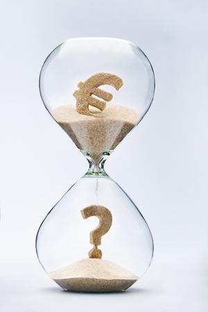 flujo: La crisis del euro. Signo de interrogación hecho de la arena que cae de la muestra de dólar que fluye a través del reloj de arena Foto de archivo