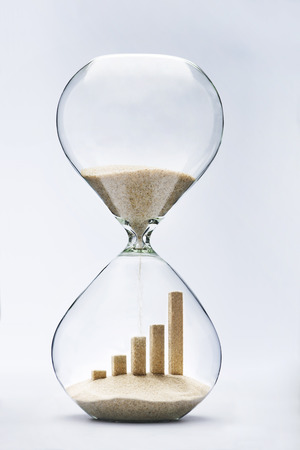 economy: Business growth graphic bar made out of falling sand inside hourglass Stock Photo
