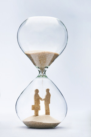 shaking out: Two businessmen shaking hands made out of falling sand inside hourglass