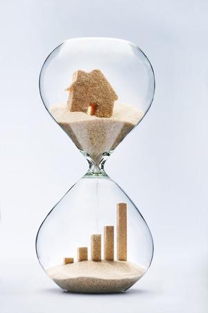 planificaci�n familiar: Concepto de bienes ra�ces. El crecimiento del negocio gr�fico de barras hechas de arena que cae desde la casa que fluye a trav�s del reloj de arena