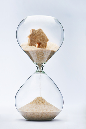 planificaci�n familiar: casa concepto de hipoteca de reloj de arena. Casa que fluye hacia abajo en el reloj de arena