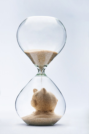 Savings concept with falling sand taking the shape of a piggy bank Stockfoto