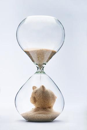 planificacion familiar: Concepto de los ahorros con la caída de la arena tomando la forma de una alcancía