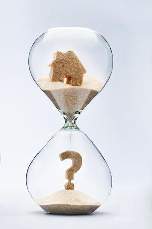 reloj de arena: Concepto de bienes raíces. Signo de interrogación hecho de la arena que cae desde la casa que fluye a través del reloj de arena