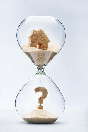 sell house: Real estate concept. Question mark made out of falling sand from house flowing through hourglass Stock Photo