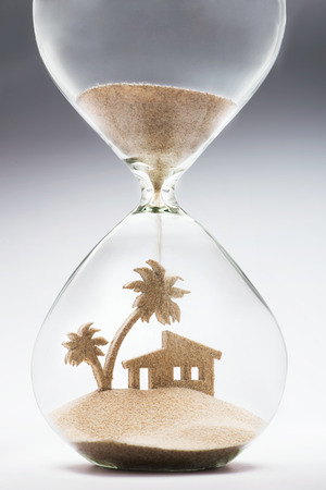Summer accomodation concept with falling sand taking the shape of a house and palm tree