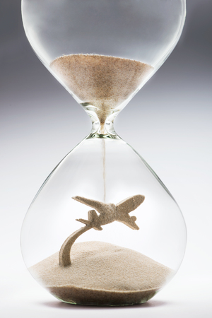 taking off: Summer travel. Hourglass falling sand taking the shape of a plane taking off